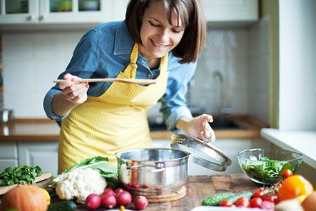 девушка пробует готовое блюдо фото